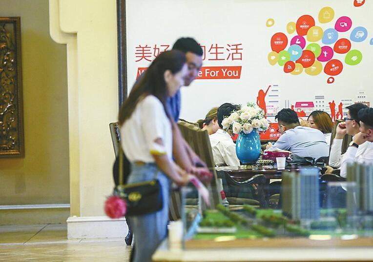 16日,西客站片区一楼盘营销中心内,中介、销售人员合力向客户荐房。 记者刘玉乐 摄